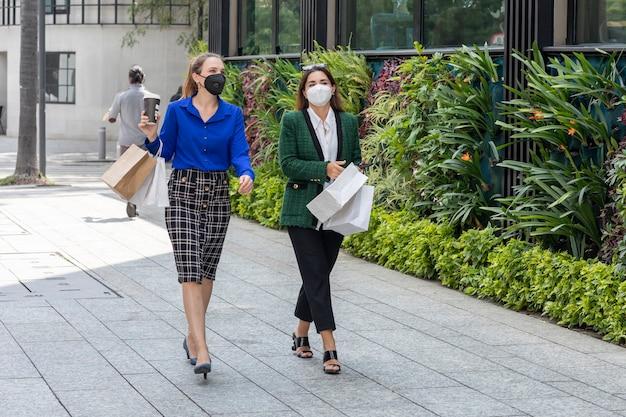 Twee jonge vrouwen lopen over straat met gezichtsmaskers die vrolijk praten na het winkelen