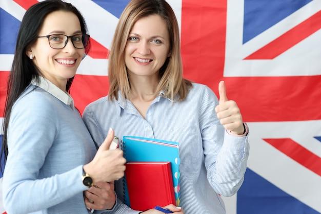Twee jonge vrouwen met boeken in handen die zich tegen achtergrond van britse vlag bevinden. leren van