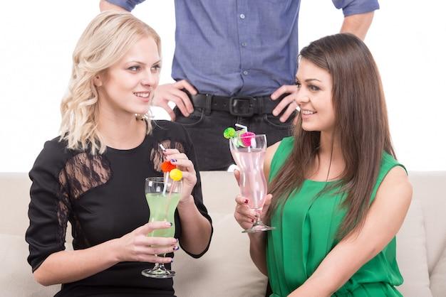 Twee jonge vrouwen met cocktails op de bank.