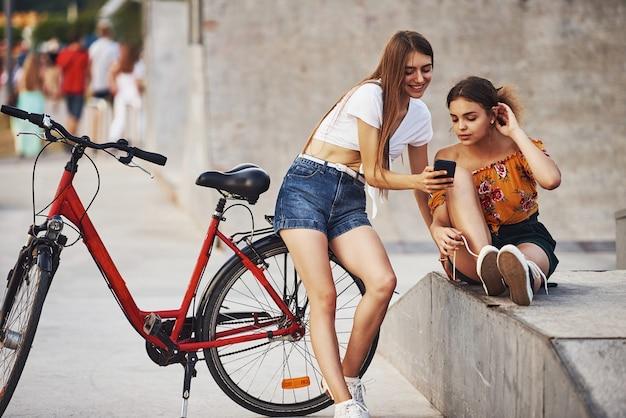 Twee jonge vrouwen met fiets hebben een goede tijd in het park bij de oprit.