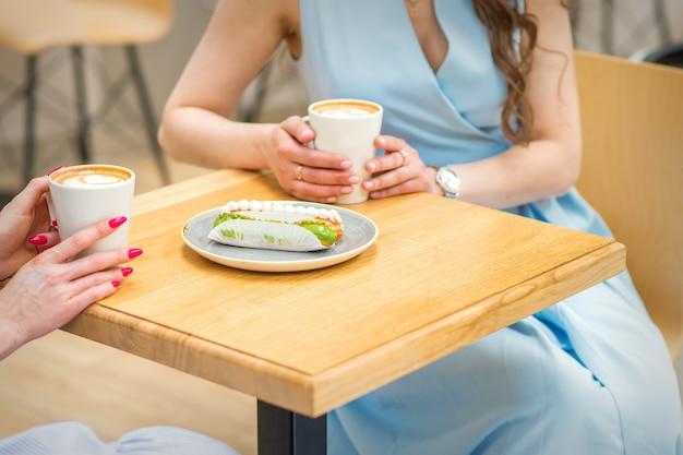 Twee jonge vrouwen met kopjes koffie en stukjes cake zitten aan tafel in een café buitenshuis