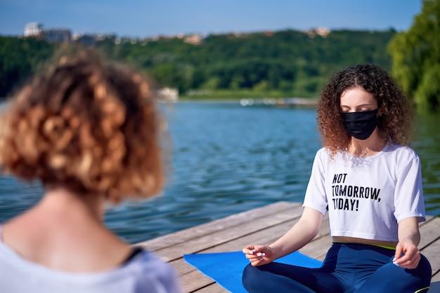 Twee jonge vrouwen met medische maskers die yoga buiten doen