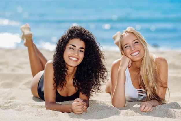 Twee jonge vrouwen met mooie lichamen in badkleding op een tropisch strand.