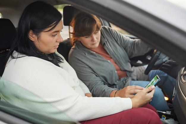 Twee jonge vrouwen met overgewicht autorijden met behulp van de navigator op de mobiele telefoon, ze kijken richting op de kaart
