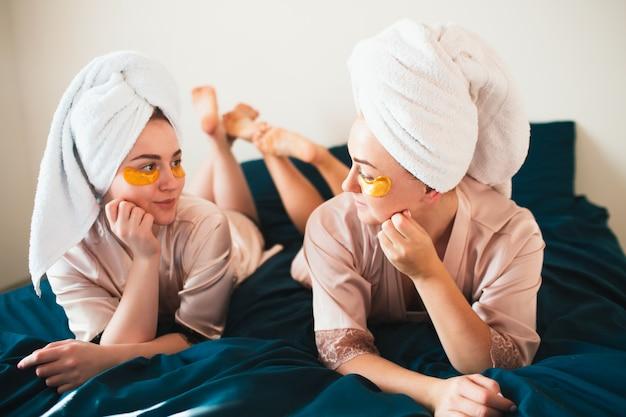 Twee jonge vrouwen met plezier met patches onder hun ogen. twee vrienden in handdoeken en pyjama's hebben samen een leuk spa-feest in huis.