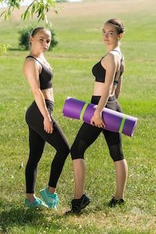 Twee jonge vrouwen met yogamatten in het park