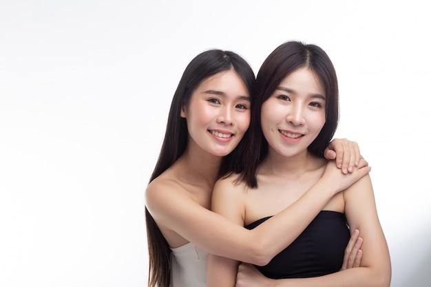 Twee jonge vrouwen omhelzen elkaar gelukkig.