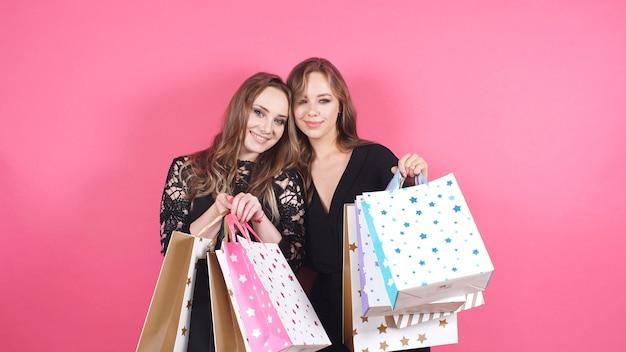 Twee jonge vrouwen poseren voor de camera in een studio met een groot aantal tassen