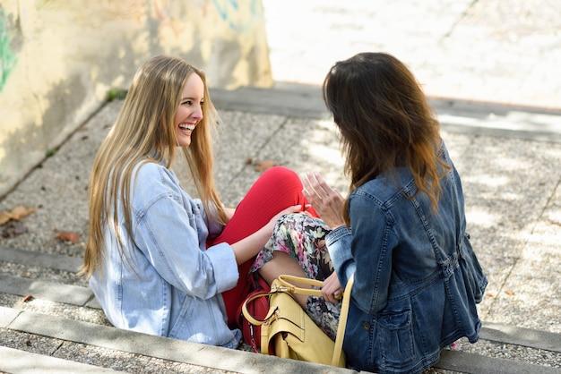 Twee jonge vrouwen praten en lachen op stedelijke stappen.