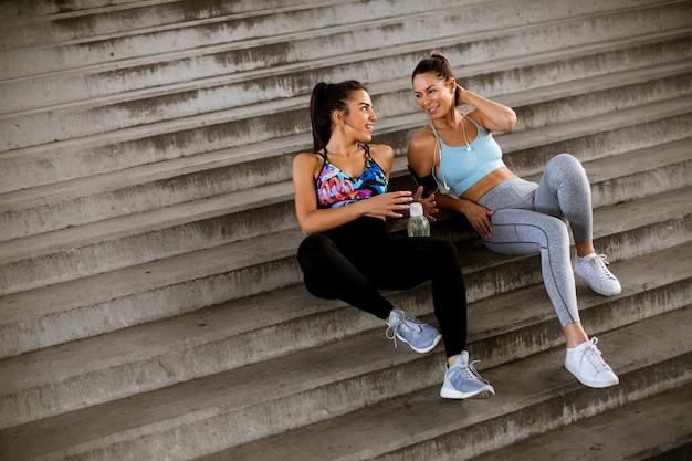 Twee jonge vrouwen rusten tijdens training met fles water in stedelijke omgeving