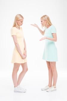 Twee jonge vrouwen ruzie. ge oleerd over witte muur
