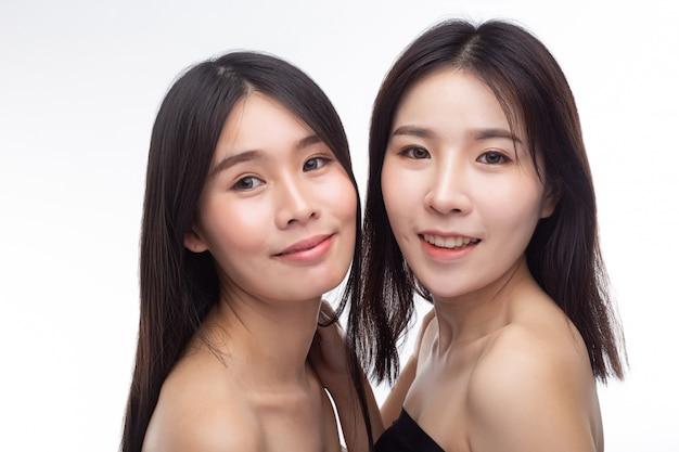 Twee jonge vrouwen staan blij tegenover elkaar.