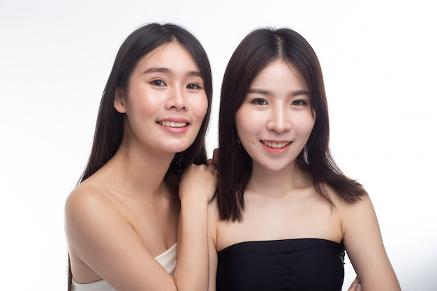 Twee jonge vrouwen stonden gelukkig van achteren bij elkaar.