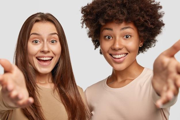 Twee jonge vrouwen van gemengd ras hebben positieve, vriendelijke uitdrukkingen, staan dicht bij elkaar