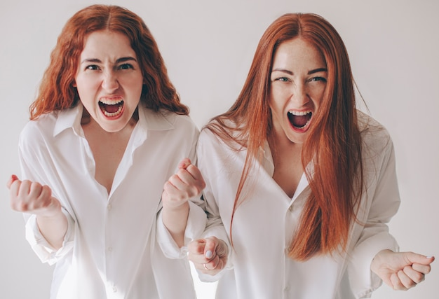 Twee jonge vrouwen werden boos en schreeuwden naar de camera ze voelen woede, agressie, woede. twee roodharige zussen staan geïsoleerd op een witte achtergrond in ruime oversized shirts