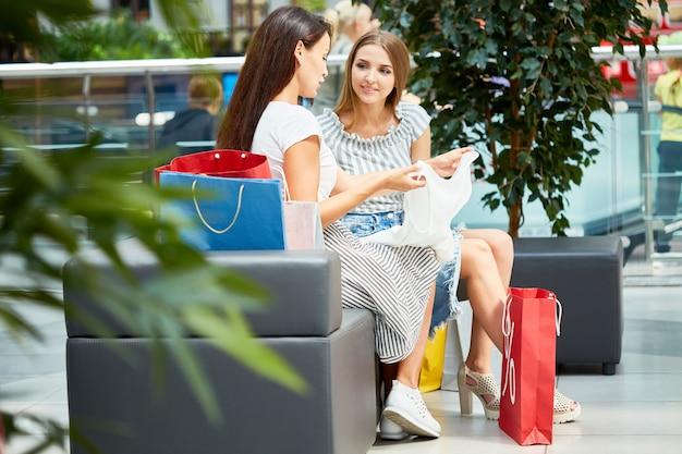 Twee jonge vrouwen winkelen voor kleding