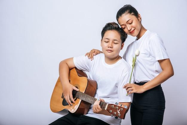 Twee jonge vrouwen zaten op een stoel en speelden gitaar.