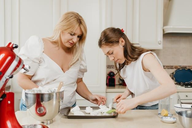 Twee jonge vrouwen zetten ijverig de opgeklopte meringue op een dienblad met een lepel en een schouderblad in de keuken. meisjes bereiden zich voor om een heerlijke taart met citroenschuimgebakje te koken.