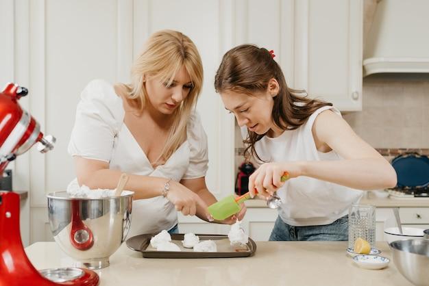 Twee jonge vrouwen zetten ijverig de versgeklopte meringue op een dienblad met een lepel en een schouderblad in de keuken. meisjes bereiden zich voor om een heerlijke taart met citroenschuimgebakje te koken.