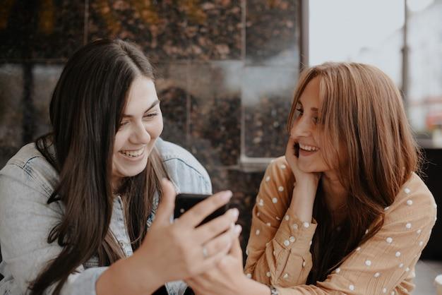 Twee jonge vrouwen zitten met een telefoon in een open café in de stad