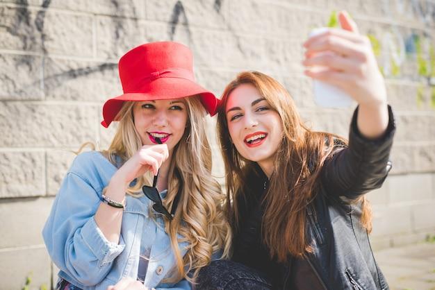 Twee jonge vrouwenvrienden die apparaten gebruiken