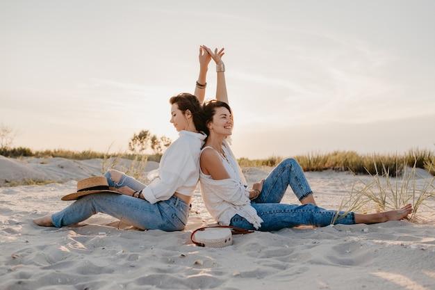 Twee jonge vrouwenvrienden die pret hebben op het zonsondergangstrand, homo-lesbische liefdesromantiek
