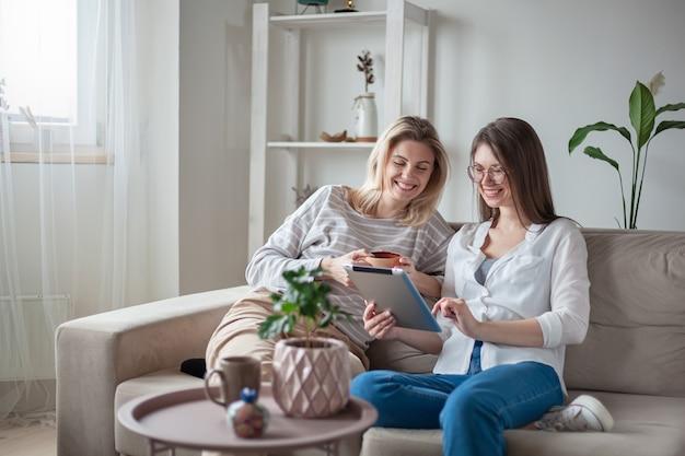 Twee jonge vrouwenvrienden die tablet samen gebruiken, zittend op de co
