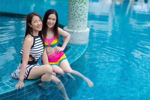 Twee jonge vrouwenvrienden genieten van in zwembad