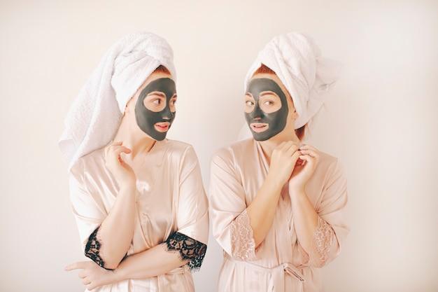 Twee jonge vrouwenzusters in badjassen met handdoeken op hun hoofd dat op een witte achtergrond wordt geïsoleerd. spa thuis. ze maken een masker voor huidverzorging op het gezicht. en aangebracht op de huid van het gezicht
