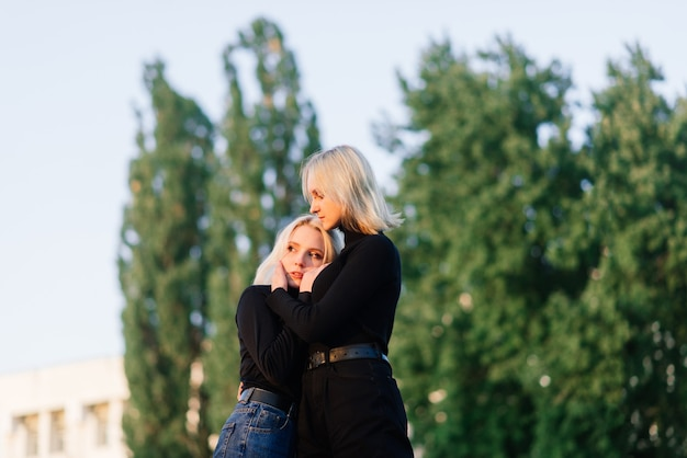 Twee jonge vrouwtjes lopen glimlachend omarmen en zoenen buiten in de stad