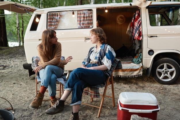 Twee jonge wandelaars die op stoelen zitten en met elkaar praten tijdens het kamperen in het bos