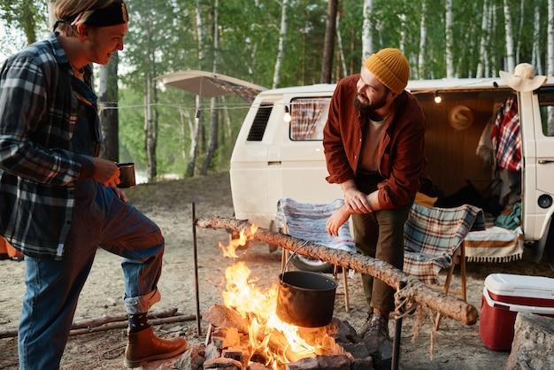 Twee jonge wandelaars die samen eten koken op een kampvuur in het bos