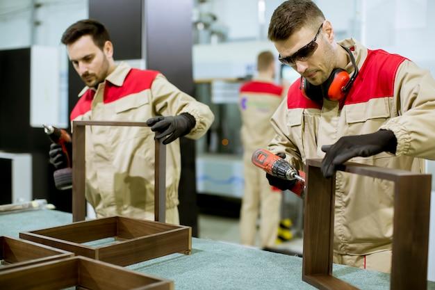 Twee jonge werknemers die meubilair in de fabriek assembleren