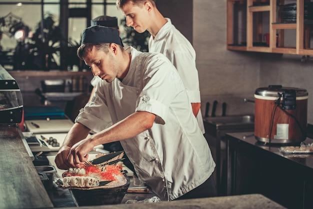 Twee jonge witte chef-koks gekleed in wit uniform versieren klaar gerecht in restaurant