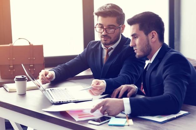 Twee jonge zakenlieden die aan laptop op modern kantoor werken. baard hipster zakenlieden. filmeffect, lensflare