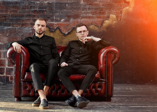 Twee jonge zakenlieden zitten op een rode leren bank in de studio. jonge ondernemers, toekomstige generatie. de geest van onafhankelijkheid. beginnen.