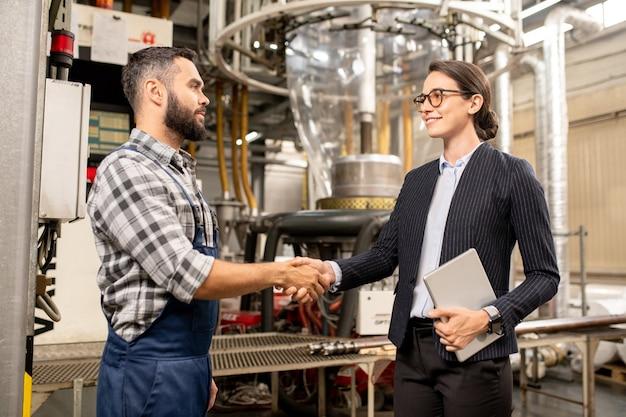 Twee jonge zakenpartners die elkaar de hand schudden na ondertekening van contract van partnerschap en productie-uitwisseling