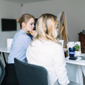 Twee jonge zakenvrouw serieus zitten in het kantoor
