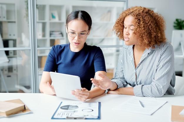 Twee jonge zelfverzekerde accountants kijken naar gegevens op touchpad-display terwijl ze deze bespreken of analyseren op werkvergadering