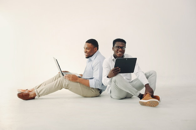 Twee jonge zwarte mannen die samenwerken en de laptop gebruiken