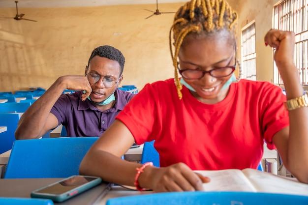 Twee jonge zwarte studenten in een klaslokaal, beide met gezichtsmaskers, gelukkig tijdens het studeren