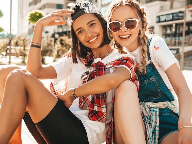 Twee jongelui die mooie meisjes met kleurrijke stuiverskateboards glimlachen. vrouwen die in de zomer hipster kleren op de straatachtergrond zitten. positieve modellen die plezier hebben en gek worden