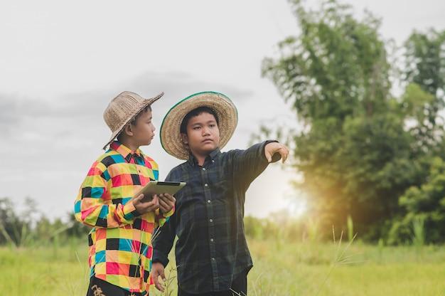 Twee jongen aziatische mensen met behulp van tablet staande deur boer, concept slimme boer of onderwijs collage studie school