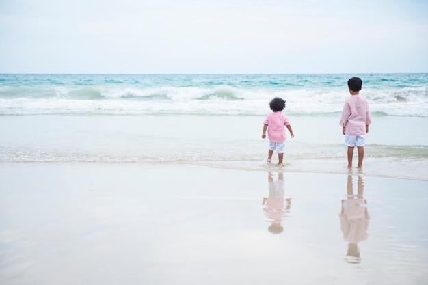 Twee jongen spelen op het strand op zomervakantie