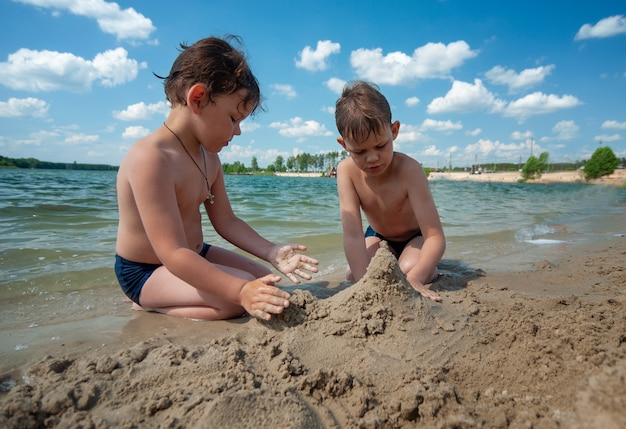 Twee jongens bouwen in de zomer tijdens het zwemmen zandkastelen op het strand
