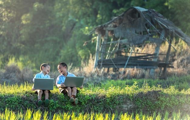 Twee jongens die door online te leren bestuderen met laptop bij openlucht, platteland van thailand