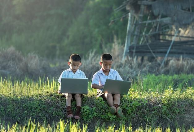 Twee jongens die een laptop in openlucht met behulp van