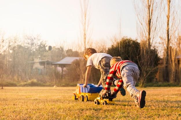 Twee jongens die met stuk speelgoed voertuigen spelen op het groene gras