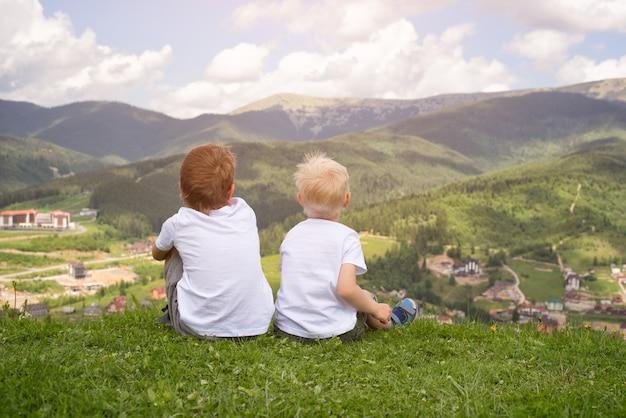 Twee jongens die op heuvel zitten en de bergen bekijken. achteraanzicht