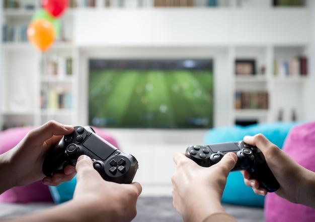 Twee jongens die thuis het spelen van videospelletjes op spelconsole zitten Premium Foto